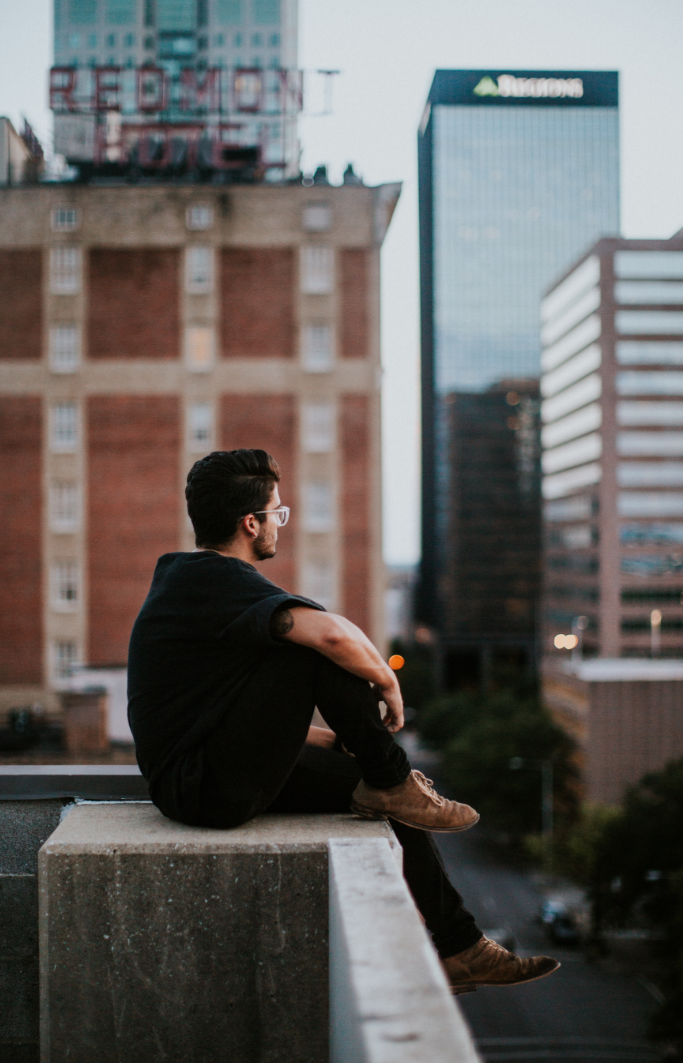 man, sitting on edge of building, looking at city